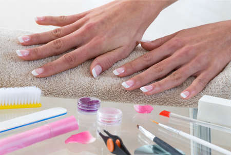 Hands of young woman with french manicure on the towel photo