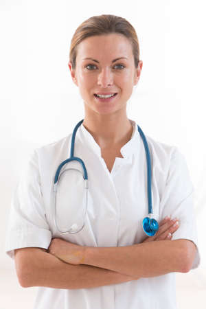 Portrait of young female doctor with arms crossed isolated on white background photo