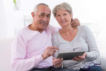 vejez feliz: feliz pareja senior con ordenador Tablet PC en casa