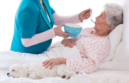elderlycare  feeding an elderly woman atretirement house, or home