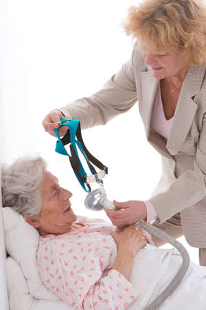 giver: care giver Adjusting CPAPmachine  to an elderly woman