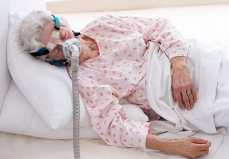 elderly  woman is sleeping with a CPAP machine photo