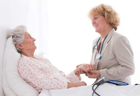 senior care: Friendly female doctor comforting a senior patient. at hospital or retierement house