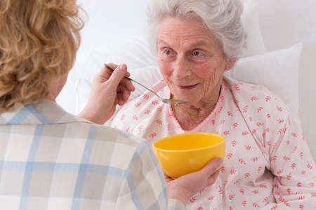 feed: Female caregiver serving dinner  to senior woman at nursing home