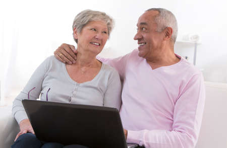 Senior couple looking information at home with computer. photo