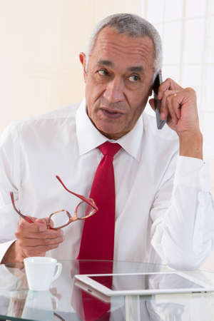 african businessman: Senior african american businessman talking on mobile phone in office
