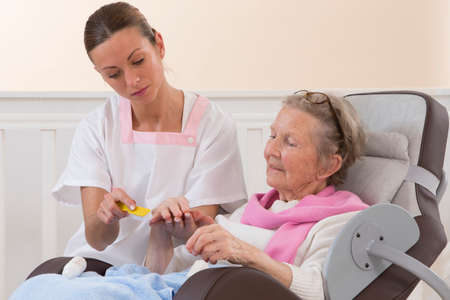 arthritic: Older senior woman receiving hand home beauty treatment Stock Photo