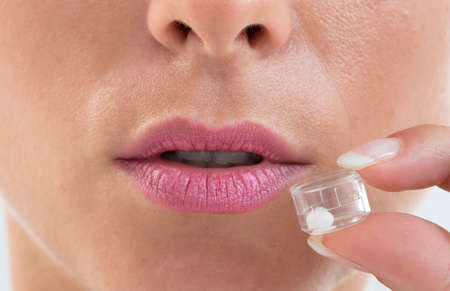 homeopatía: Mujer viradas píldoras homeopatía jóvenes