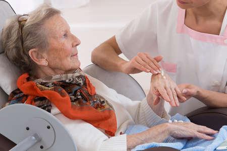 Verpleegkundige of verzorger helpt een bejaarde vrouw met huidverzorging en hygiëne maatregelen thuis Stockfoto