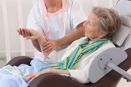 Verpleegkundige of verzorger helpt een bejaarde vrouw met huidverzorging en massage thuis Stockfoto