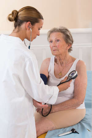 sphygmomanometer: Female doctor measuring blood pressure of senior woman Stock Photo