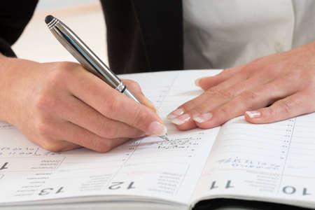 Zakenvrouw in het kantoor te merken van een afspraak in haar dagboek, close-up