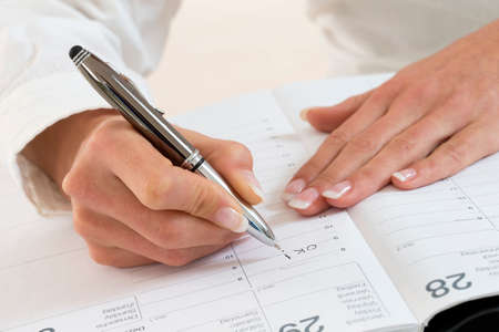 Businesswoman in office noting an appointment in her diary, closeup
