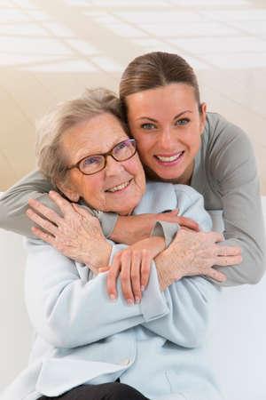 Oma en kleindochter. Jonge vrouw zorgt voor een oudere vrouw. Stockfoto