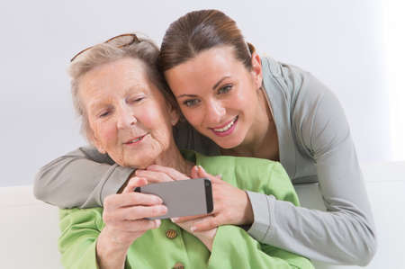 Grand-Mother and attractive young grand-daughter photographing themselves by mobile phone, smiling happily. photo