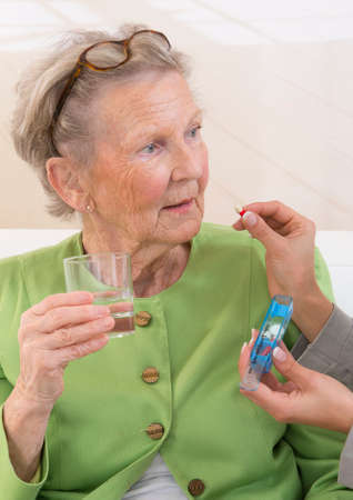giver: Care giver or nurse giving to elderly woman her pills