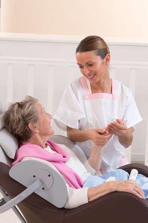 enfermeria: Enfermera o cuidador ayuda a una anciana con las medidas de cuidado de la piel y de higiene en el hogar
