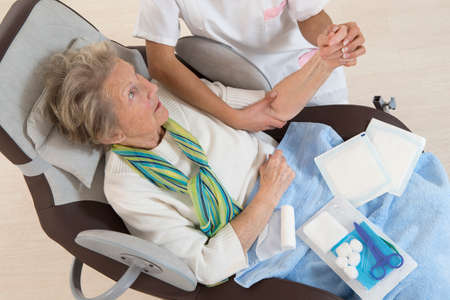 Nurse taking care of senior woman in retirement home bandaging her arm 스톡 콘텐츠
