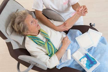 herida: Enfermera que toma el cuidado de la mujer mayor en la casa de retiro de vendar su brazo