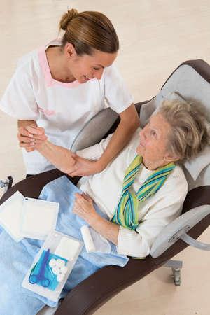 bandaged: Nurse taking care of senior woman in retirement home bandaging her arm Stock Photo