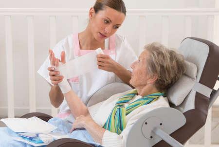 Verpleegkundige verzorging van senior vrouw in rusthuis verbandmiddelen haar arm