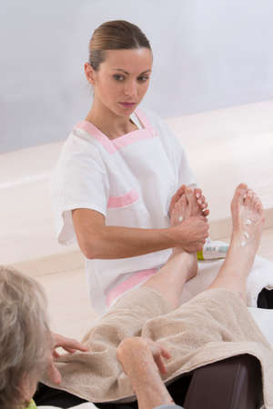 chiropodist: Nurse or care giver massaging foot   of an elderly woman Stock Photo