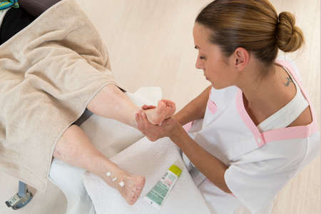 care giver: Nurse or care giver massaging foot   of an elderly woman Stock Photo