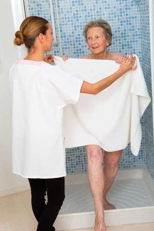 assisting: Care giver or nurse  assisting elderly woman for shower