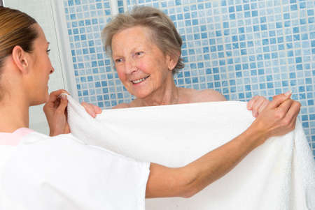 giver: Care giver or nurse  assisting elderly woman for shower