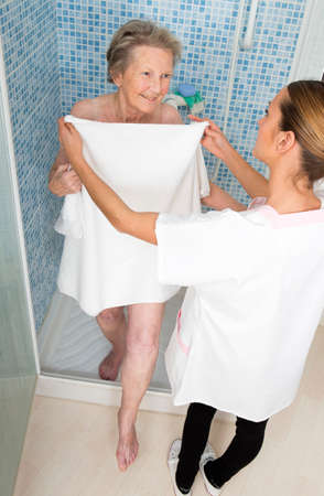 Care giver or nurse  assisting elderly woman for shower