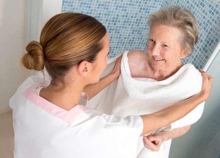 Verzorger of verpleegkundige helpen oudere vrouw naar de douche