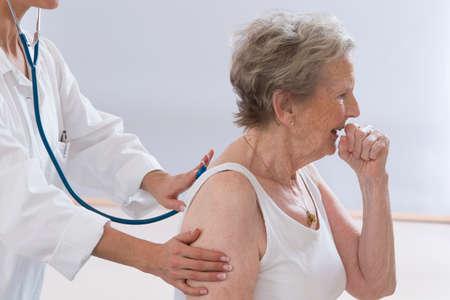 persona sentada: Mujer mayor toser mientras doctor le examina Foto de archivo