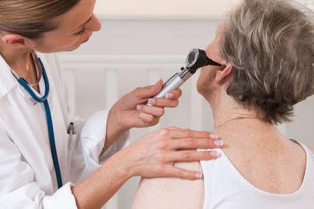 otoscope: doctor examining elderly patients ears Stock Photo