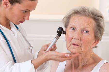doctor examining elderly patients ears Stock Photo