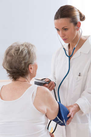 blood pressure gauge: Female doctor measuring blood pressure of senior woman Stock Photo