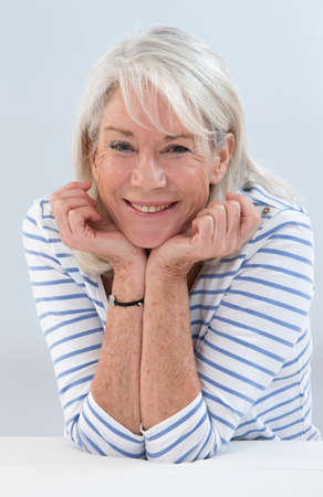 senior woman: portrait of pretty senior woman with hands on her face Stock Photo