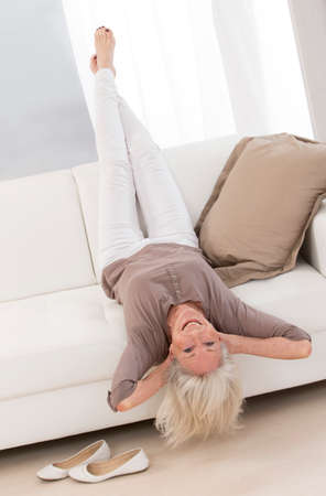 comfort room: Elegant Senior woman relaxing on a sofa with head upside down