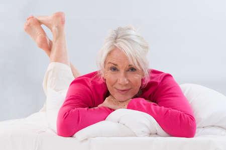 woman white shirt: Beautifull Senior Woman in pink shirt Relaxing On Bed