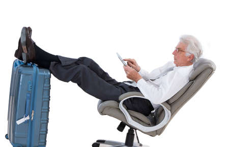 business lounge: business man holding a digital tablet  while sitting in the airport in business lounge  sitting with foot on his luggage
