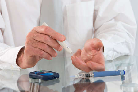 onset: Business man in his office  with  onset diabetes measuring blood sugar with indicator