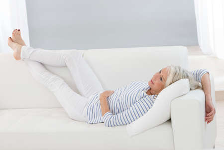 Smart senior woman relaxing at home on the sofa legs Lifted -Flexible, sporty