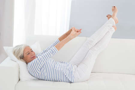 lifted: Smart senior woman relaxing at home on the sofa legs Lifted -Flexible, sporty