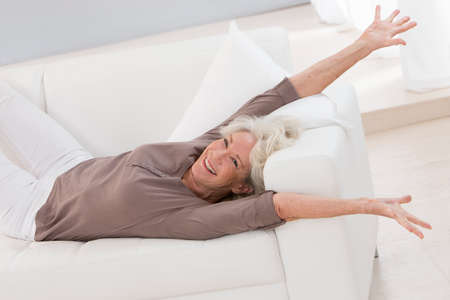 stretch: beautiful senior woman relaxing at home in her bed arm up and stretching