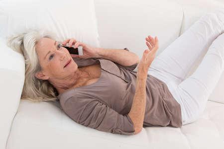 65 years old: Senior woman talking on mobile phone