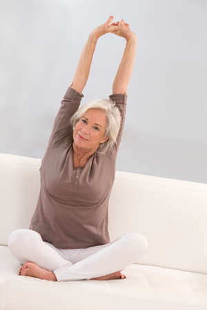 brigh: beautiful senior woman relaxing at home in her bed arm up and stretching