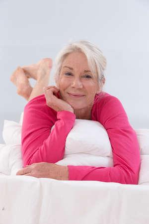 senior woman: Beautifull Senior Woman in pink shirt Relaxing On Bed