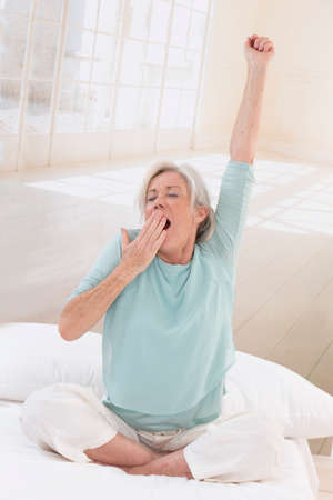 women s health: beautiful senior woman relaxing at home in her bed arm up and stretching