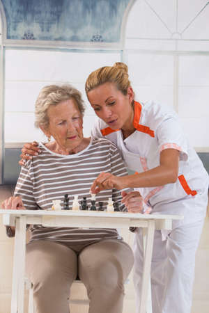 retirement: Senior woman playing checkers with a nurse in a retirement home Stock Photo