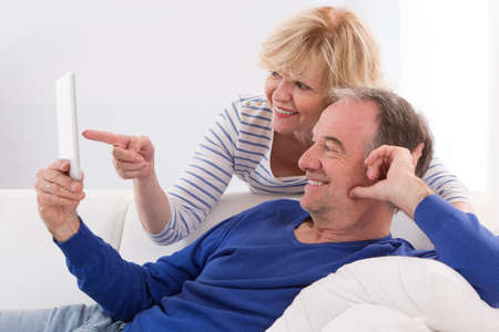 persona leyendo: encantadora pareja madura con tablet PC en casa