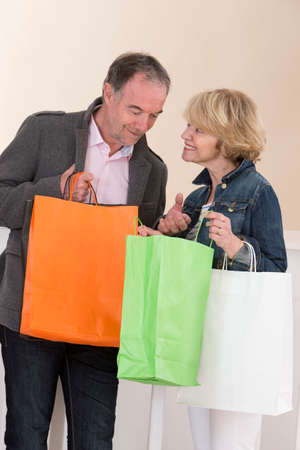sale shop: Happy Mature Couple Holding Multi Colored Shopping Bags Stock Photo